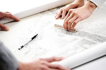 Plan auf einem Tisch, zwei Personen arbeiten daran