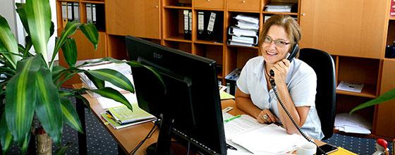 Sekretärin mit Telefon in der Hand sitzt hinter ihrem Schreibtisch im Büro