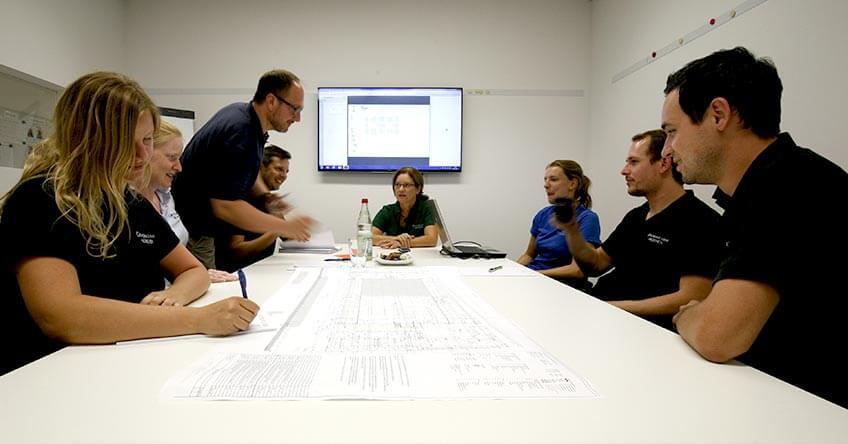 Schlichter Besprechungsraum mit Monitor an der Wand und einem großen Tisch mit Mitarbeitern