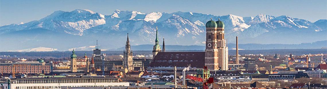 Blick über die Stadt München, im Hintergrund die Alpen