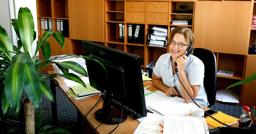 Sekretärin mit Telefon in der Hand sitzt hinter ihrem Schreibtisch im Büro und telefoniert