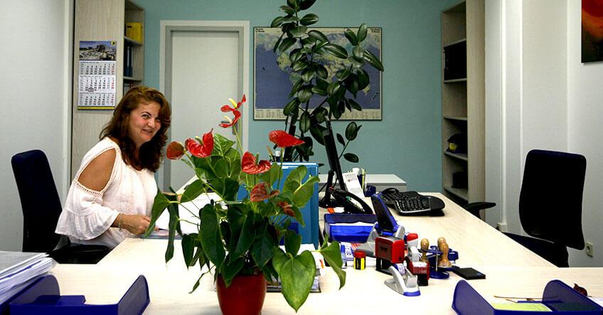 Sekretärin sitzt am Schreibtisch und sortiert Unterlagen