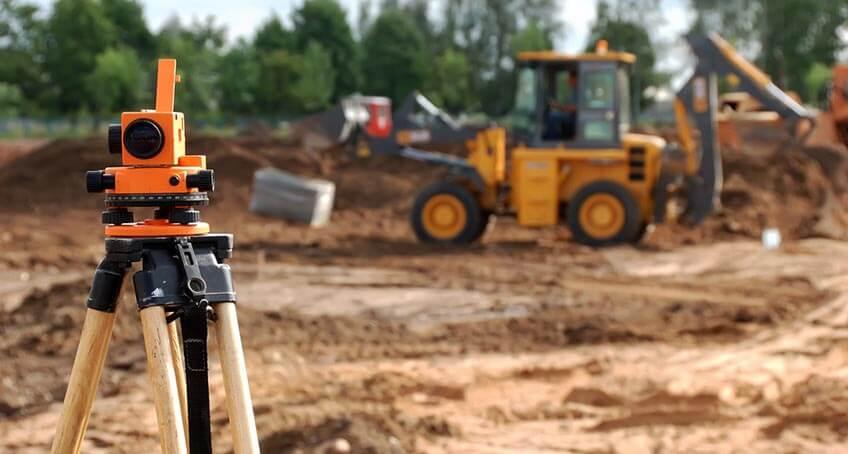 Vermessungsgerät auf einer Baustelle, im Hintergrund ein Bagger